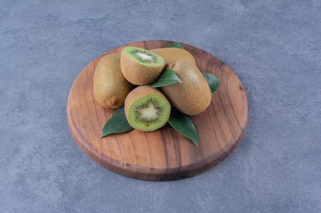 Gesneden en hele kiwi's aan boord op marmeren tafel.