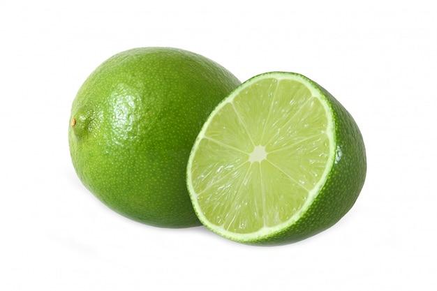 Gesneden en hele limoen fruit geïsoleerd op een witte achtergrond met uitknippad