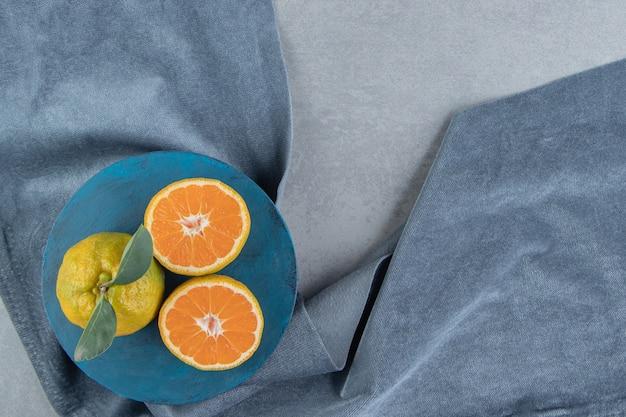 Gesneden en hele mandarijnen op een blauw bord op een stuk stof, op marmer