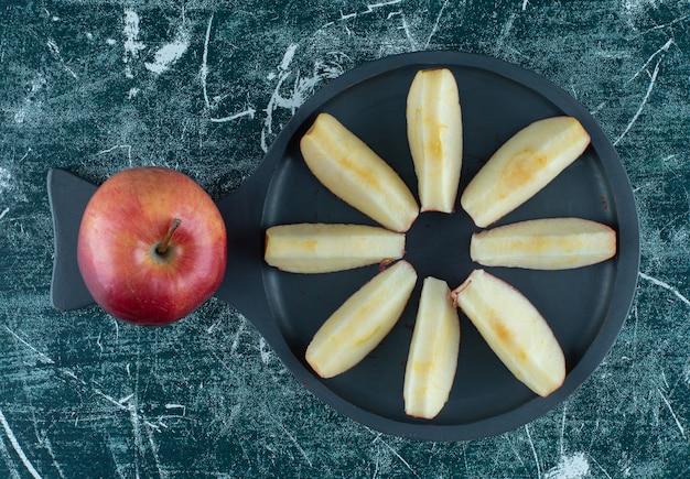 Gesneden en hele rode appel op donkere houten bord.