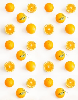 Gesneden en hele sinaasappelen op een lichte ondergrond