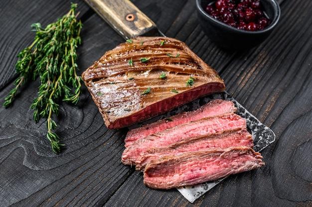 Gesneden flank of bavette beef steak op een hakmes. zwarte houten achtergrond. bovenaanzicht.