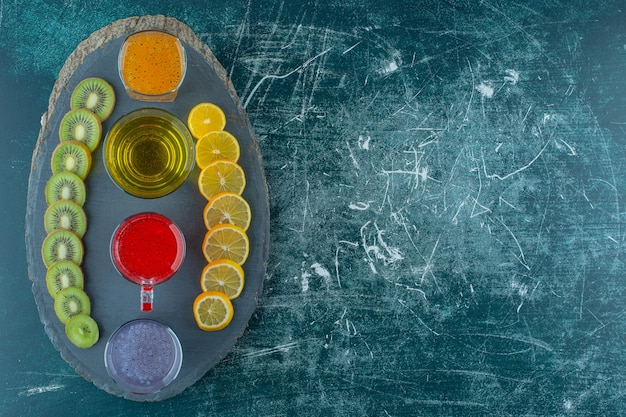 Gesneden fruit en een glas sap op het bord, op de blauwe achtergrond. Gratis Foto