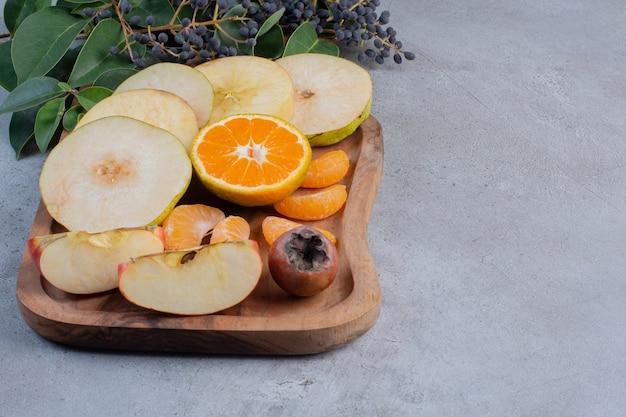 Gesneden fruit gebundeld op een houten bord op marmeren achtergrond.