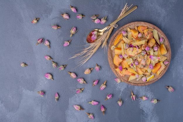 Gesneden fruitschaal met bloemen op blauw.