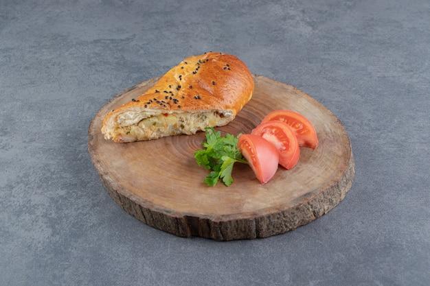 Gesneden gebak gevuld met kaas op stuk hout.