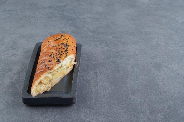 Gesneden gebak gevuld met kaas op zwarte plaat.