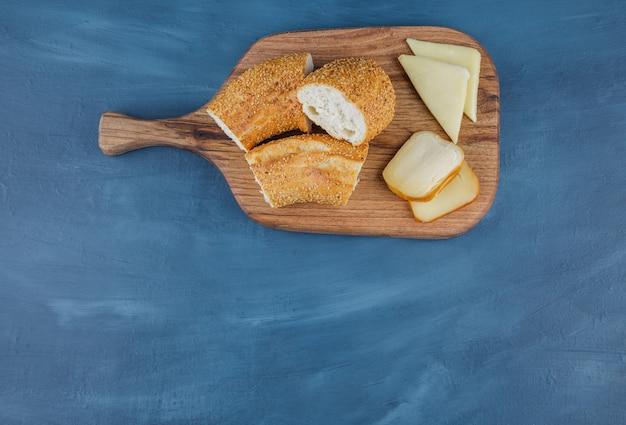Gesneden gebak met kaas en gesneden gele kaas op een houten bord.