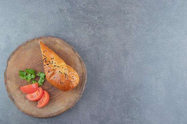 Gesneden gebakje gevuld met kaas op stuk hout.