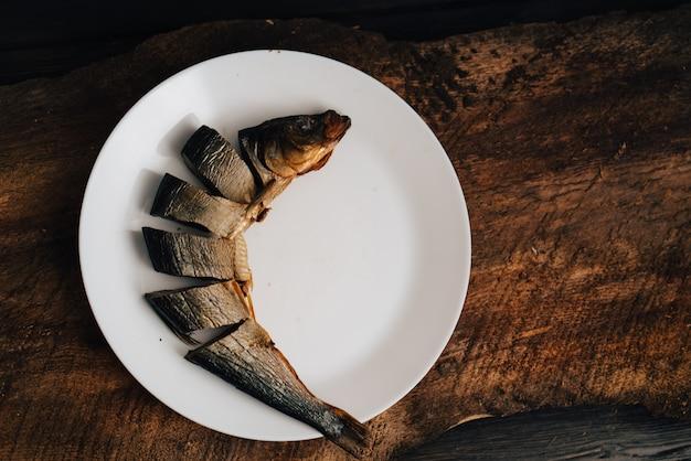 Gesneden gedroogde vis op een witte plaat op een houten tafel