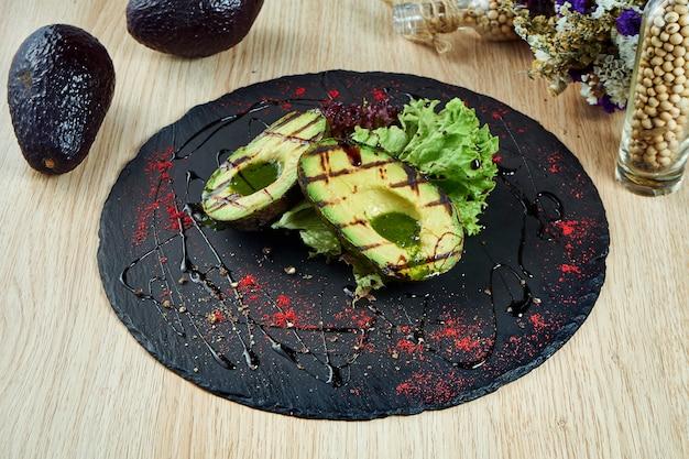 Gesneden gegrilde avocado op zwarte leisteen bord met kruiden en zwarte saus. visie. gezond eten voor de lunch