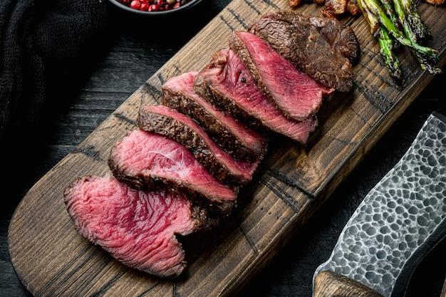 Gesneden gegrilde gemarmerd vlees steak filet mignon set, met ui en asperges, op houten serveerplank, met vleesmes en vork, op zwarte houten tafel
