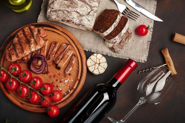 Gesneden gegrilde varkenssteaks met een fles wijn, wijnglas, kurkentrekker, mes, vork, zwart brood, cherrytomaatjes, knoflook