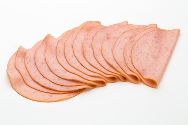 Gesneden gekookte hamworst die op witte achtergrond wordt geïsoleerd.