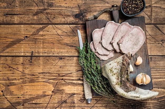 Gesneden gekookte rundvleestong met kruiden. houten tafel. bovenaanzicht.