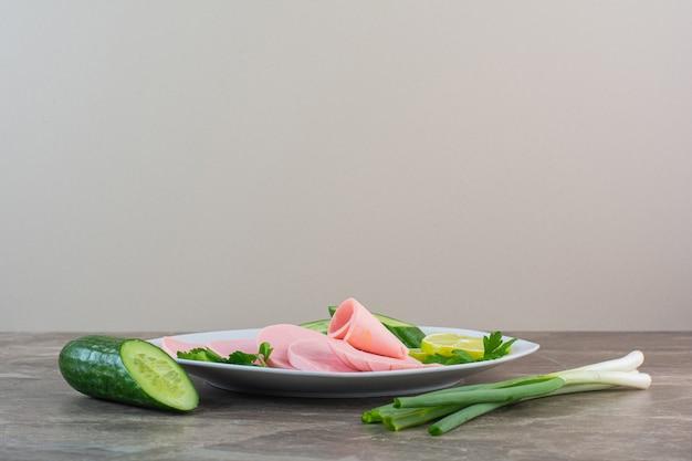 Gesneden gekookte worst, peterselie, komkommer en groene uien op een bord, op de marmeren achtergrond.