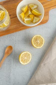 Gesneden gele citroen op kommen en pot