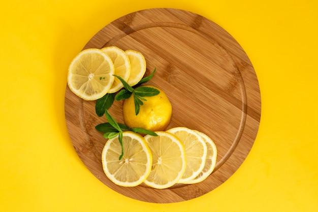 Gesneden gele citroenen op een bruin houten bord, ernaast ligt een bosje groene munt, zomerdranken