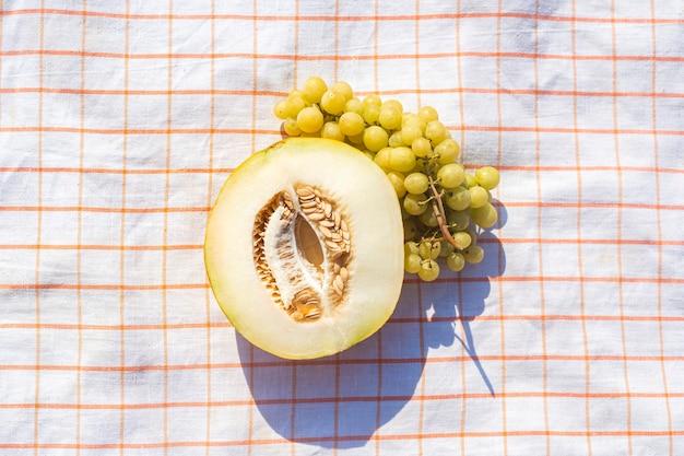 Gesneden gele meloen, druiven op een tafelkleed op het strand. bovenaanzicht, plat gelegd.