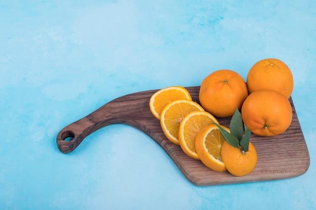 Gesneden gele sinaasappelen op een houten schotel op blauw.