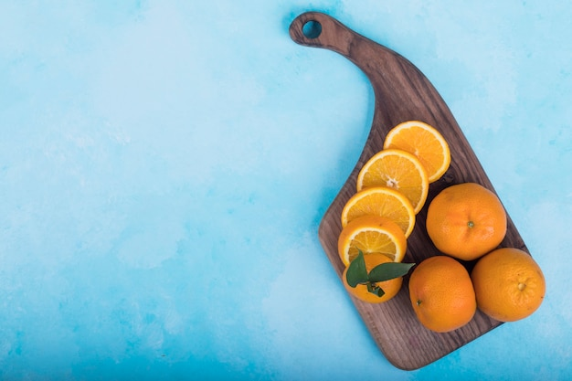 Gesneden gele sinaasappelen op een houten schotel op blauw