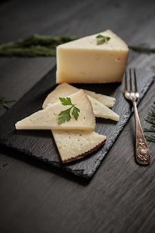 Gesneden genezen kaas en vork op zwarte achtergrond