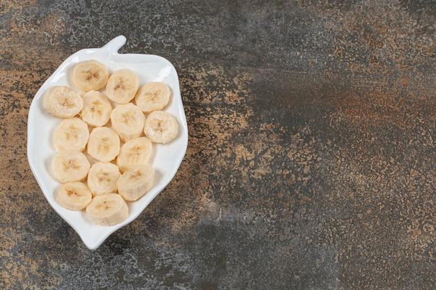 Gesneden gepelde bananen op witte plaat.