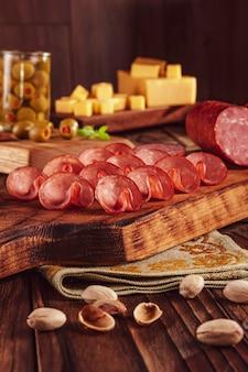 Gesneden gerookte salami op een snijplank met blokjes kaas, olijven, kastanjes en pistachenoten