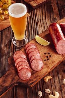 Gesneden gerookte salami op een snijplank met een glas bier, olijven, kastanjes en pistachenoten