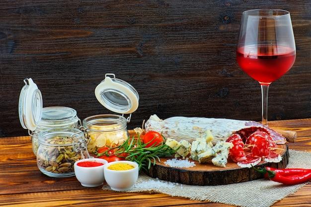 Gesneden gerookte worst met kruiden en een glas rode wijn op donkere houten rustieke achtergrond.