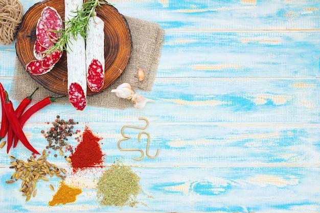 Gesneden gerookte worst met kruiden en een takje rozemarijn op blauwe houten rustieke achtergrond.