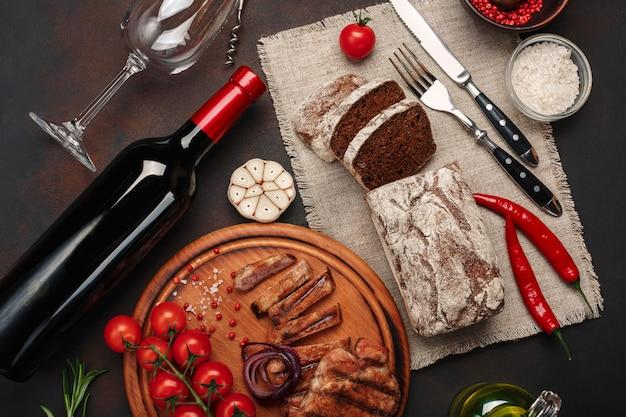 Gesneden geroosterde varkensvleeslapjes vlees met fles wijn, wijnglas, kurketrekker, mes, vork, zwart brood, kersentomaten