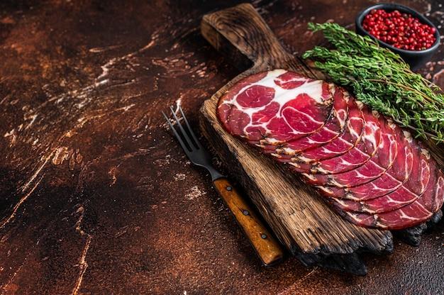 Gesneden gezouten coppa ham op een houten bord met tijm. donkere achtergrond. bovenaanzicht. kopieer ruimte.