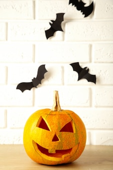 Gesneden gloeiende pompoen en zwarte vleermuizen op lichte achtergrond. halloween feest.