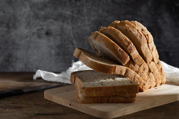 Gesneden graan volkoren brood op donkere rustieke houten achtergrond, bio ingrediënten, gezonde voeding.