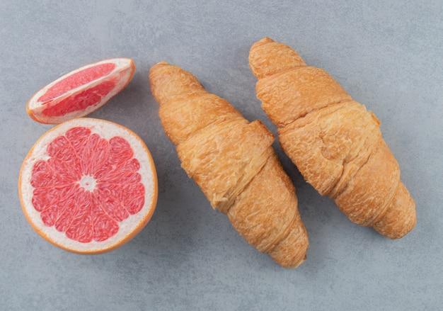 Gesneden grapefruit en croissant op de marmeren achtergrond. hoge kwaliteit foto