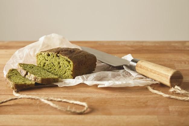Gesneden groen rustiek gezond brood van spinaziedeeg geïsoleerd met antiek mes op houten snijplank