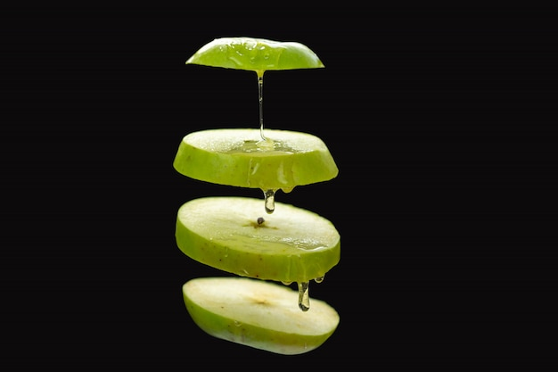 Gesneden groene appel zweven op zwarte achtergrond met vloeibare honing druppels