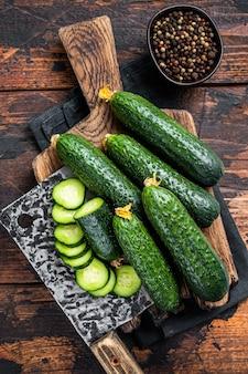 Gesneden groene komkommers op een houten snijplank. donkere houten achtergrond. bovenaanzicht.