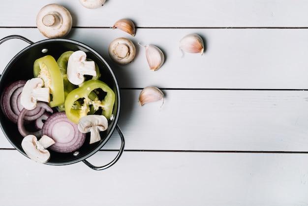 Gesneden groene paprika; champignons en uien in de pan met knoflookteentjes op houten plank
