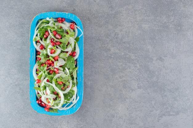 Gesneden groenen, uien en granaatappelzaden op blauw bord. hoge kwaliteit foto