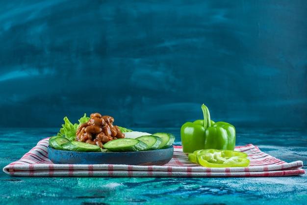 Gesneden groenten en gebakken bonen op een houten plaat op een handdoek, op de blauwe achtergrond.