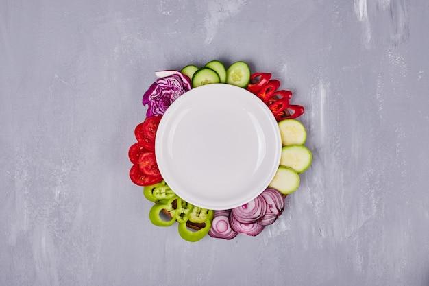 Gesneden groenten en kruiden in een witte plaat.