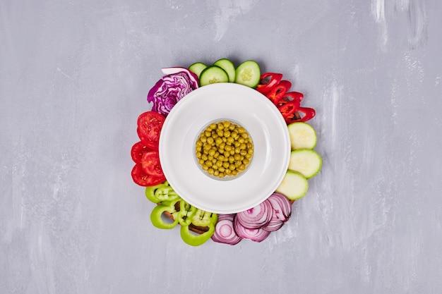 Gesneden groenten en kruiden in een witte schotel, bovenaanzicht.