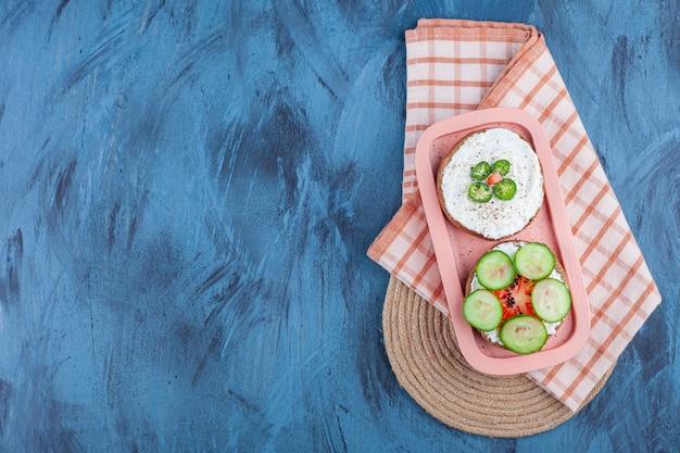 Gesneden groenten op kaasbroodjes in boord op handdoek op onderzetter op blauw.