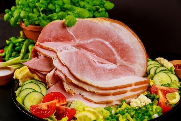 Gesneden ham met verse salade close-up. bovenaanzicht.