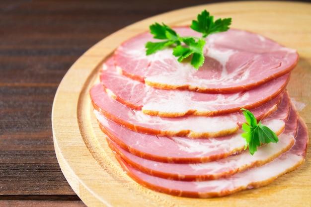 Gesneden ham verse groene slabladeren op een ronde snijplank.