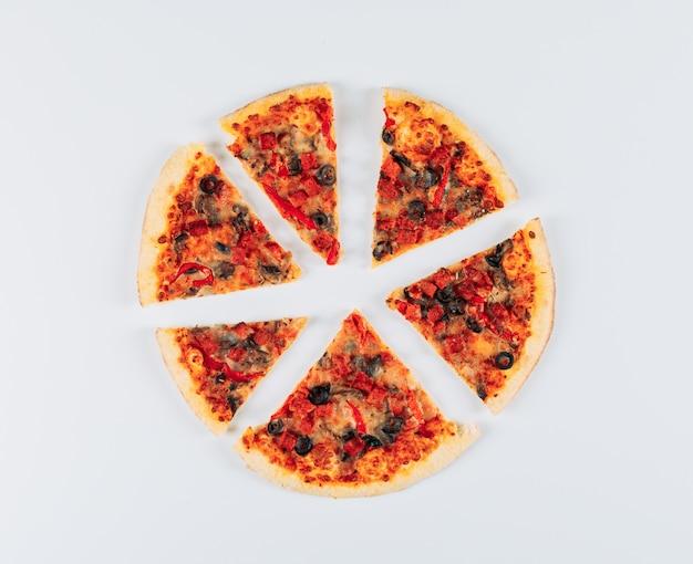 Gesneden hartige pizza op een licht blauwe stucwerk achtergrond. plat lag.