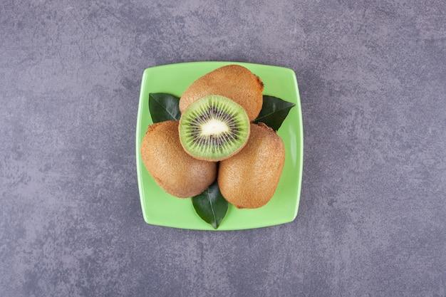 Gesneden heerlijke kiwi met bladeren die op een groene plaat worden geplaatst.