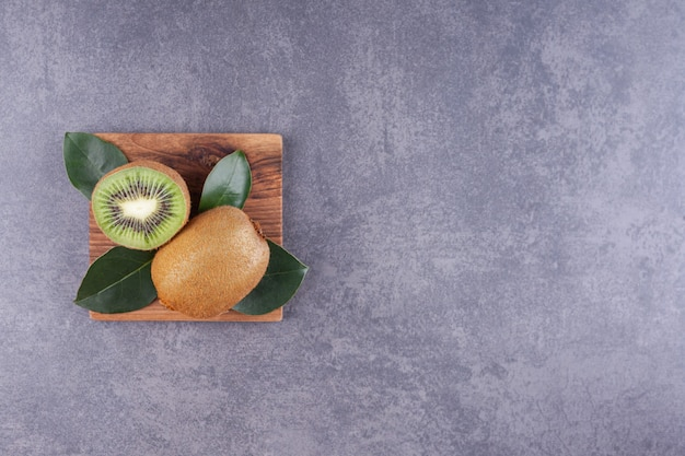 Gesneden heerlijke kiwi met bladeren die op een houten plaat worden geplaatst.
